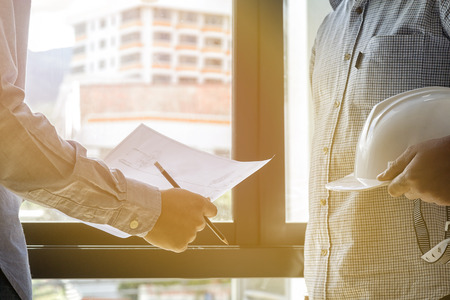 executive helmet: Architects look at paper plan business with sunlight Stock Photo