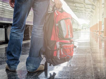 mochila de viaje: Parte inferior de viajero con mochila en la estación de tren. el concepto de viaje.