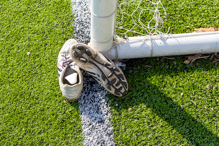 Old soccer Shoes on artificial turf field with goal Stock Photo