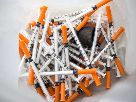 Close up of used syringes in the trash Standard-Bild