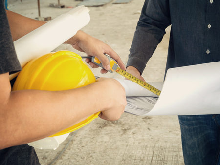 foreman: Engineer discussing with foreman about project in building construction site Stock Photo
