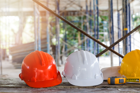 guard house: Helmet and blueprint on table on construction site Stock Photo
