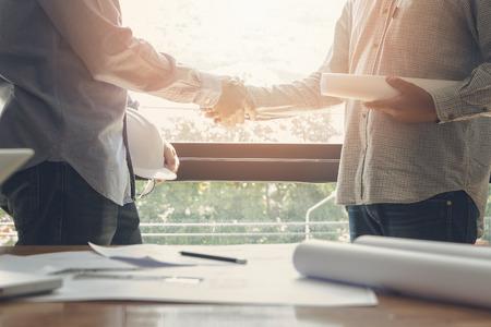 Architect and engineer shaking hands beside the window Standard-Bild