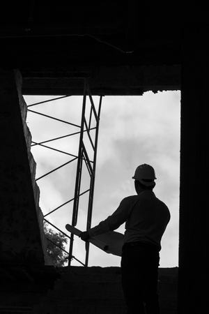 architect tools: Monochrome image of Engineer with blueprint in building construction site