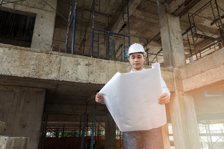 architect tools: Engineer with blueprint in building construction site
