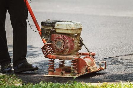 Worker uses vibratory plate compactor compacting asphalt at road repair