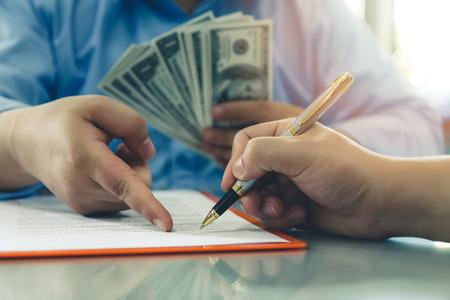 男は、100 ドル札のバッチを提供しています。契約契約、ビジネス契約の詳細を行うビジネスマンのクローズ アップ。