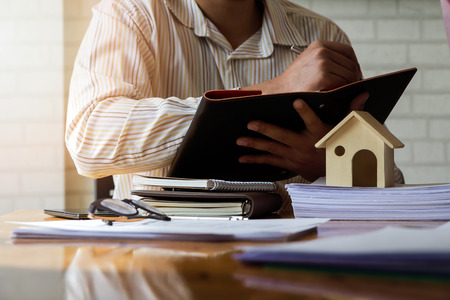 Architect working in a office. Architect writing somthing on notebook about house project in office, architectural concept