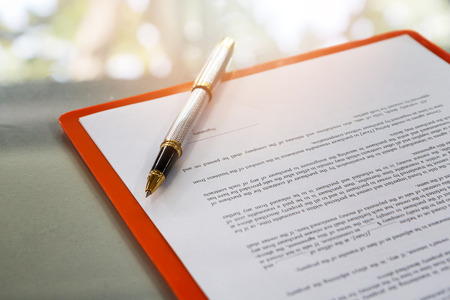 A pen on contract paper preparation for signing a contract.
