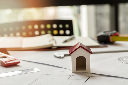 details: A architects house model with plan and blueprints on architect desk Stock Photo