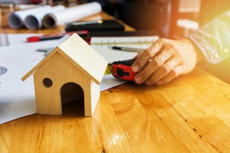 Architects house model and blueprints on architect desk with architect