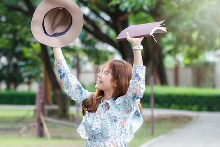 Young asian woman in retro dress push her hands up with hat and book in park Stock Photo
