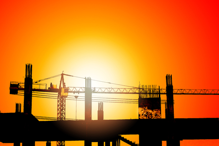 Silhouette of lifting crane and building in construction site high ground over sunset background