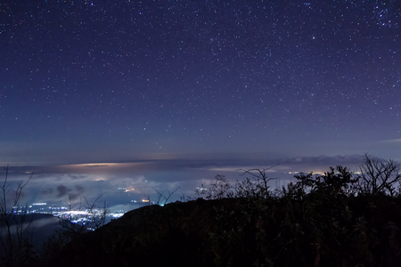 Night view with stars over clouds and the mountain