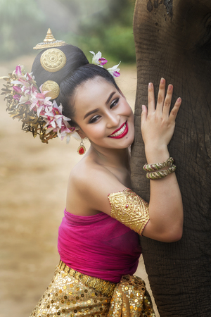 Pretty thai girl in traditional thai dress with elephant