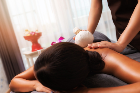 Masseur doing back massage with compress in spa salon. Beauty treatment concept. Standard-Bild - 112676787