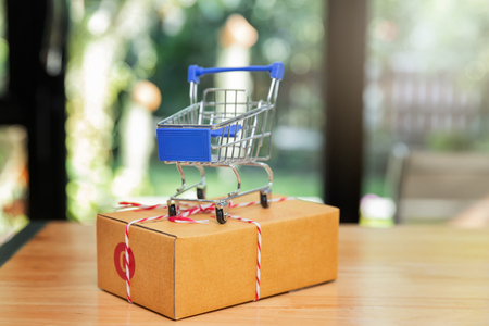 Close up of miniature shopping carts on parcel box. Modern payment systems. Online shopping and e-commerce concept. Standard-Bild - 112676790