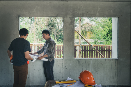 Engineer and architect discussing with foreman about project in building construction site Standard-Bild - 112676795