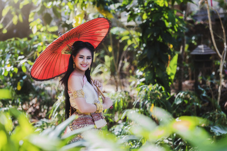 Beautyful Thai woman wearing thai traditional clothing with red umbrella. Standard-Bild - 112676812