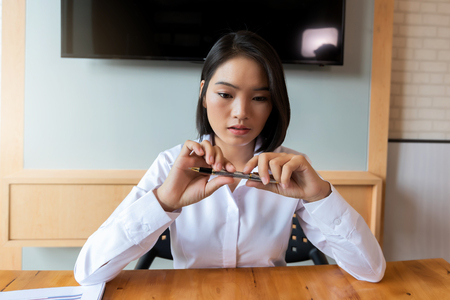 Beautiful young Asian woman holding a pen in her hand. Business concept. Standard-Bild - 112676813
