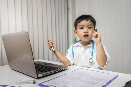 Little boy in medic uniform pointing finger up with successful idea, Careers in children's dreams concept. Standard-Bild - 112676817