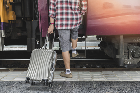 Traveler with baggage is stepping up the train in train station. Transportation concept. Standard-Bild - 112676832