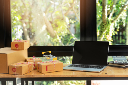 Cardboard parcel box and laptop ondesk at workplace of startup small business owner for online selling. Standard-Bild - 112676836