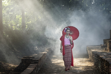 Beautiful Thai woman wearing thai traditional clothing with red umbrella in amid the smoke and fog. Standard-Bild - 112676841