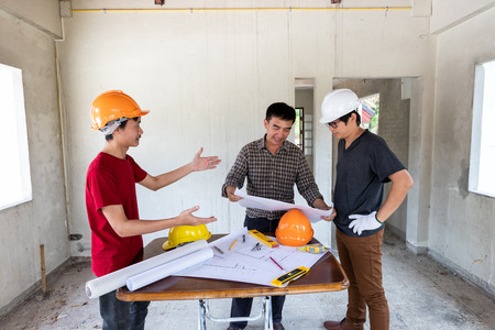 Engineer and architect discussing with foreman about project in building construction site Standard-Bild - 112676880