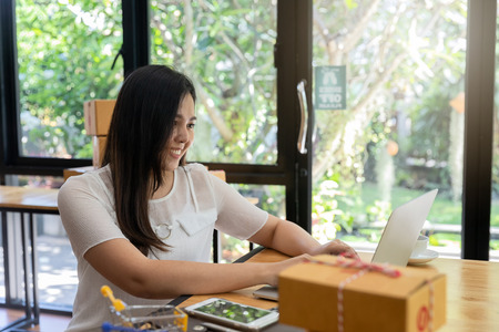 Successful entrepreneur business woman with online sales and Parcel shipping in her home office. Woman checking order on laptop. Standard-Bild - 112676884