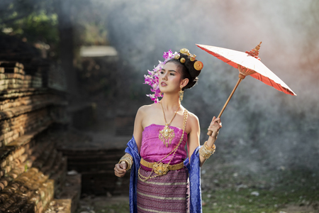 Beautiful Thai woman wearing thai traditional clothing with red umbrella in amid the smoke and fog. Standard-Bild - 112676885