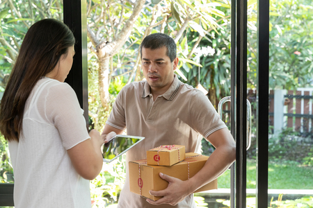 Delivery service worker in uniform delivering parcel to recipient. Woman signing e-document on tablet. Standard-Bild - 112676901