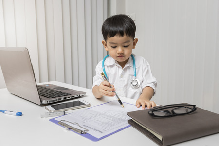 little boy in medic uniform using a pen on desk Standard-Bild - 112676899