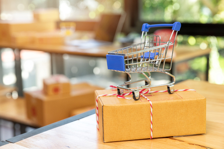 Close up of miniature shopping carts on parcel box. Modern payment systems. Online shopping and e-commerce concept. Standard-Bild - 112676936