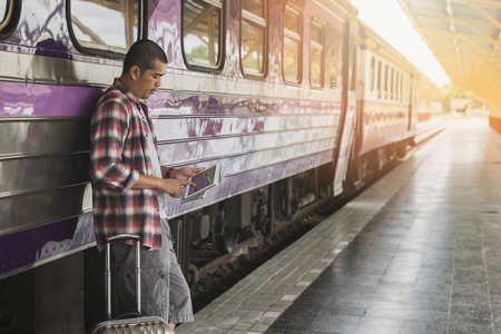 Traveler with baggage and digital tablet in train station. Travel concept. Standard-Bild - 112676946