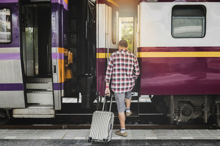 Traveler with baggage is stepping up the train in train station. Transportation concept. Standard-Bild - 112678335