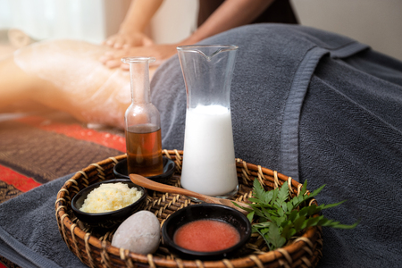 Skin care products and a cosmetic body scrub in basket with Spa therapist applying scrub salt and cream on woman back. Beauty treatment concept. Standard-Bild - 112676966