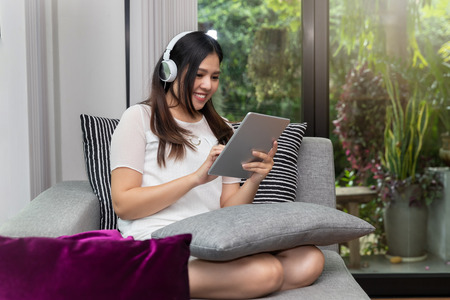 Pretty smiling young woman wear headphones sitting on sofa and usinging on tablet. Standard-Bild - 112676973