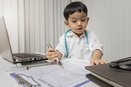 little boy in medic uniform using a pen on desk