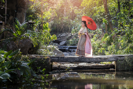 Beautyful Thai woman wearing thai traditional clothing with red umbrella. Standard-Bild - 116539701