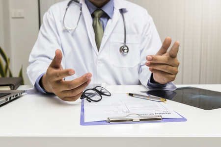 A doctor consults patient while sitting at the table in office. Medicine and health care concept. Standard-Bild - 116539899