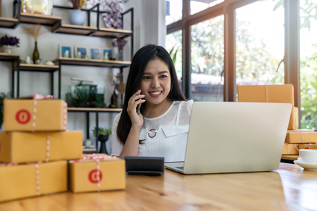 Woman are receiving orders via cell phone. Successful entrepreneur business woman with online sales and Parcel shipping in her home office. Standard-Bild - 116539900