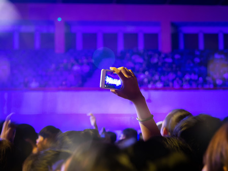Some cheering fans take a photograph or video with smartphone in a free live concert. Standard-Bild - 116539901