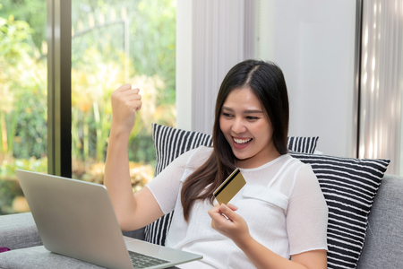 Happy asian woman holding credit card in the gesture yes!. She was excited and glad of success while online shopping. E-commerce and modern technology concept. Standard-Bild - 116539911