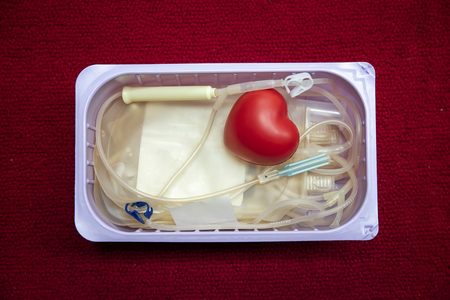 A red heart bouncy ball with blood bag in basket. Healthcare and charity. Blood donation concept Standard-Bild - 116539921