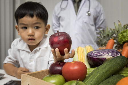 Children and doctors happy to have healthy food.Kid learning about nutrition with doctor to choose eating fresh fruits and vegetables. Foto de archivo