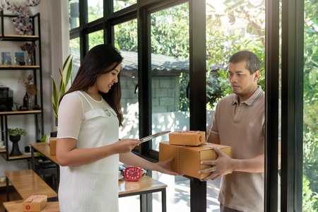 Woman received the parcel delivery to the house. Woman signing to get her package.