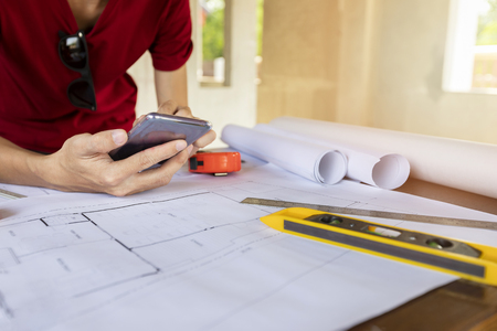 Engineer or Architect using cell phone on blueprint in building construction site. Standard-Bild - 116540145
