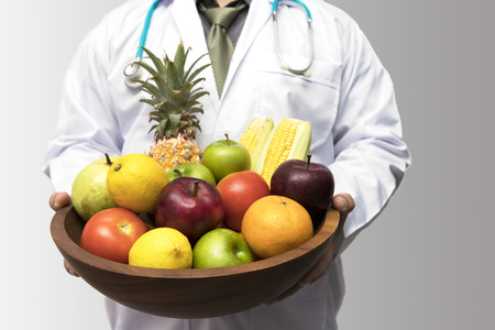 Doctor holding basket assort fresh fruits and vegetables isolated on white background. Standard-Bild - 116540143