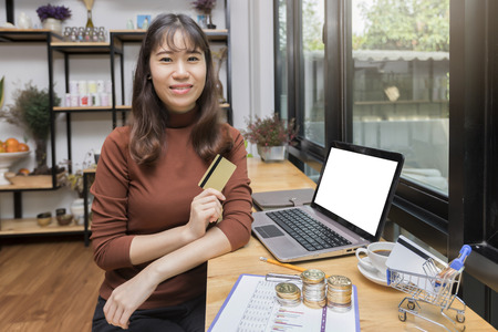 Beautiful Asian woman holding credit card and using laptop computer for online shopping. Internet shopping lifestyle, Ecommerce shipment service, SME sale promotion advertise concept. Standard-Bild - 116540144